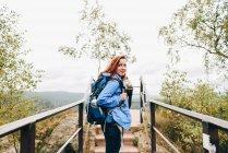 Женщина, ходить на мостик в природе в холодную погоду — стоковое фото