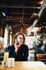 Молодая женщина, с помощью телефона, сидя в кафе за столом — стоковое фото