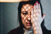 Портрет молодой женщины, охватывающих лицо рукой — стоковое фото