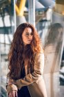 Redhead woman with baggage at window — Stock Photo