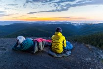 Two people sitting on the mountains at sunset — Stock Photo
