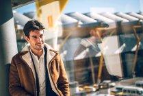 Веселий чоловік у вікні програми в аеропорту — стокове фото