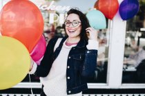 Smiling woman standing with colorful party balloons — Stock Photo