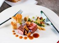 Pork dish on white plate, closeup view — Stock Photo