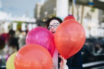 Smiling Young woman standing with colorful party balloons — Stock Photo