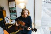 Mujer tocando la guitarra acústica en su casa junto a la ventana de cristal - foto de stock