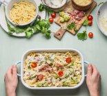 Mani di colpo direttamente sopra di un essere umano che prepara il cibo su una tabella — Foto stock