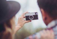 Vue arrière du couple floue prenant selfie avec appareil photo argentique vintage — Photo de stock