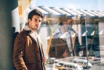 Модний чоловік у коричневий жакет постановки в аеропорту — стокове фото
