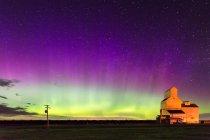 Здание под яркий зеленый фиолетовый ночного неба, сияния в Канаде — стоковое фото