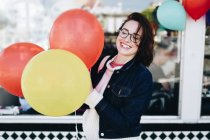 Woman standing with colorful party balloons — Stock Photo