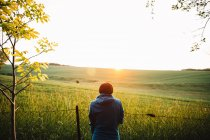 Rear view of woman standing in field on and looking at sun on horizon — Stock Photo