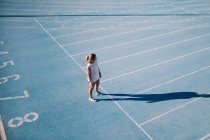 Young female athlete on blue running track — Stock Photo