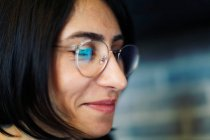 Close-up portrait of smiling woman in glasses — Stock Photo