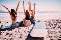 Rear view of Three girls sitting together at the beach — Stock Photo