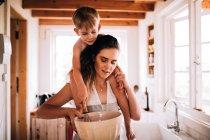 Счастливая семья, выпечки дома, мать и сын приготовления пищи в кухне и проведение чаши — стоковое фото