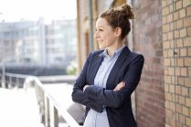 Smiling young woman standing with crossed arms at brick building wall — Stock Photo