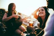 Amigos fazendo piquenique e ouvir música tocada na guitarra — Fotografia de Stock