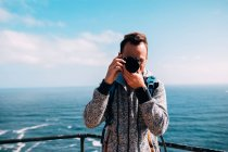 Молода людина, фотографування стоячи морем води — стокове фото