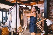 Fashion designer hanging dress in showroom — Stockfoto