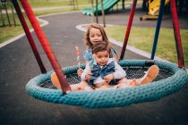 Children playing on swing in park — Stock Photo
