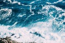 Waves splashing on sea shore, water surface background — Stock Photo