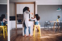 African Mother and daughter baking at home in kitchen — Stock Photo