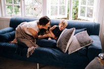 Mother and son spending time together on sofa at home — Stock Photo