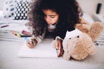 Little girl doing homework on bed — Stock Photo