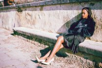 African woman in fur coat sitting on stone bench at wall — Stock Photo