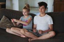 Брат и сестра, играя видеоигры на диване у себя дома — стоковое фото