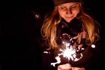 Жінка холдингу sparkler вночі — стокове фото