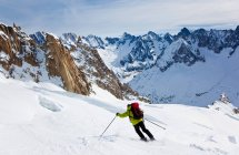 Rear view of male skier moving down the slopes — Stock Photo