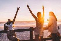 Дівчаток, які пили пиво на пляжі на заході сонця — стокове фото