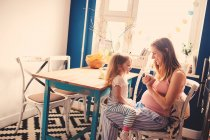 Mother and daughter sitting in kitchen together and playing — Stock Photo