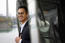 Happy smiling young businessman in city street — Stock Photo