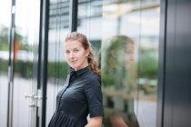 Кавказький жінка позує і дивлячись на камеру, стоячи в будівлі на вулиці — стокове фото