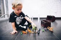 Little caucasian Boy playing with dinosaur toys at home — Stock Photo