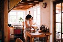 Щаслива сім'я випічки вдома, мати і син приготування їжі на кухні за столом — стокове фото