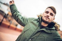 Handsome young man in green parka jacket looking at camera — Stock Photo