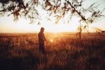 Hunter man in sunset field with rifle and cartridges — Stock Photo