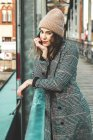 Beautiful woman in winter clothes at railing, woman wearing warm hat and autumn coat — Stock Photo