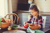 Adorable petite fille à la table de la cuisine cuisson cuisson salade aux légumes — Photo de stock