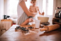 Mother and son cooking in kitchen at table, focus on foreground — Stock Photo