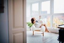 Jovem mulher sentada na cadeira confortável por uma janela em casa dentro de casa — Fotografia de Stock