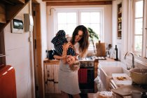 Happy young woman holding son at kitchen and playing — Stockfoto