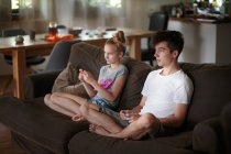 Siblings playing video games on sofa at home — Stock Photo