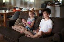 Frères et sœurs, jouer à des jeux vidéo sur canapé à la maison — Photo de stock