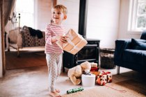 Cute boy playing with Christmas presents at home and wearing pyjama — Stock Photo