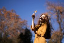 Young redheaded model woman in yellow dress holding autumn leaf — Stock Photo